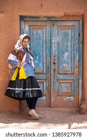 Young beautiful Iranian lady in traditional clothing in a traditional village of Abyaneh in Iran