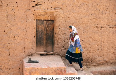 young beautiful Iranian lady in traditional clothing walking in a traditional village of Abyaneh in Iran
