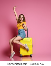 young, beautiful joyful woman, sits on a tourist suitcase, rejoices and raised her hand up. Travel concept.