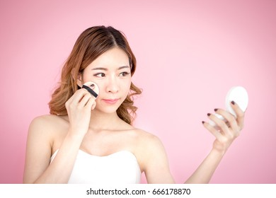 Young beautiful korea woman using product in hand at pink background, 20-30 year old.