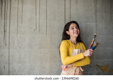 Young beautiful lady artist in apron with paint stains in her loft artistic studio