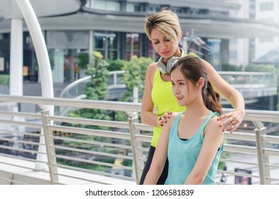 Young beautiful lady beginning yoga practice with private teacher at street city, working out with professional female yogi instructor. Trainer helps student to do  exercise.