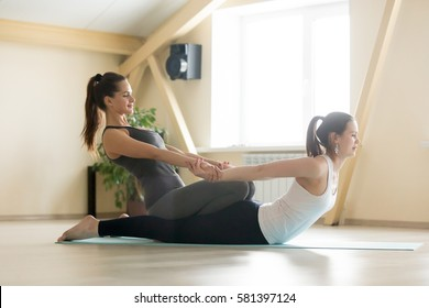 Young beautiful lady beginning yoga practice with private teacher at home, class, working out with professional female yogi instructor. Yoga trainer helps student to do spinal exercise, Locust pose