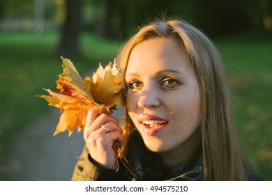 Young beautiful lady with bunch of maple leaves smiling in light of autumnal sunset