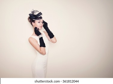 Young beautiful lady dressed in a proper outfit for horse racing with hat and gloves, fashion on the field, vintage matte effect