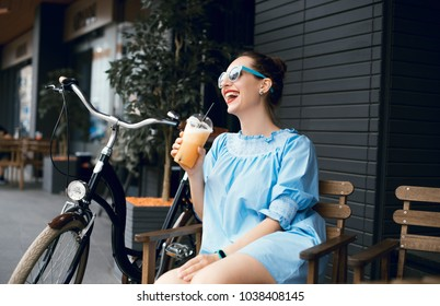 Young beautiful lady drinking fresh smoothies on a sunny summer day during her ride. Riding a bicycle in the city. Bicycle tourism. Refreshing fruit drink. Active rest.  Hipster on a bike.