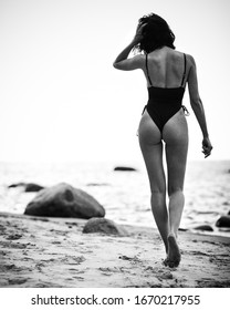 Young beautiful lady with fit body in black swimsuit walks on a sandy beach, rear view, in monochrome