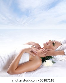Young beautiful lady getting spa treatment over sea and sky background