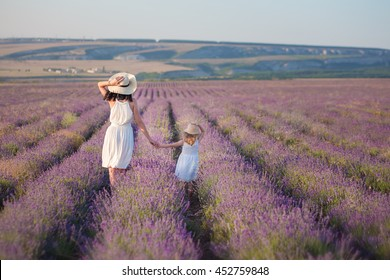 Young beautiful lady mother with lovely daughter walking on the lavender field on a weekend day in wonderful dresses and hats.