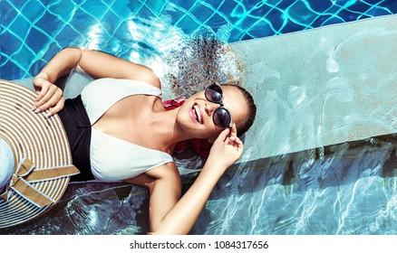 Young beautiful lady posing at swimming pool