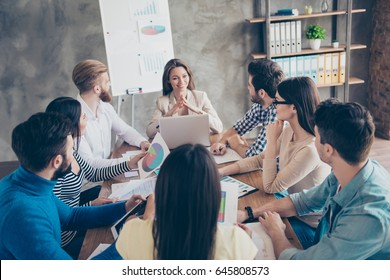 Young beautiful lady is reporting to the team about the development of the company at the meeting. Collegues are listening to her with attention