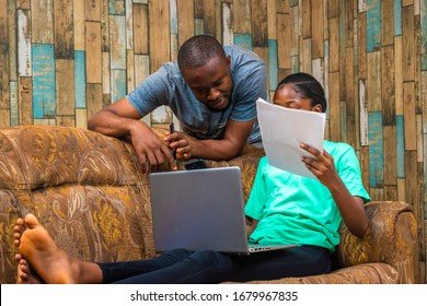 young beautiful lady sitting on a couch and working on her laptop and a guy behind her holding some documents