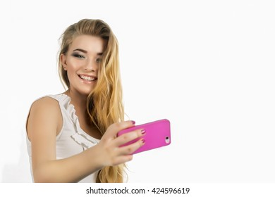 Young beautiful lady taking a selfie self portrait of herself smiling at he camera.Pretty hipster girl taking selfie. Close up portrait of a attractive woman holding a smartphone digital camera.