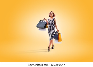 young beautiful lady walking after successful shopping. She smile and carry colour packages in their hands. colour background