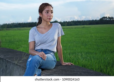 Young beautiful Lady watching the sun by the ricefield.