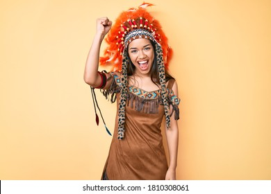 Young beautiful latin girl wearing indian costume angry and mad raising fist frustrated and furious while shouting with anger. rage and aggressive concept.