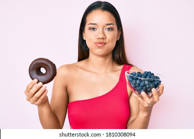 Young beautiful latin girl wearing swimsuit holding donut and blueberries puffing cheeks with funny face. mouth inflated with air, catching air.