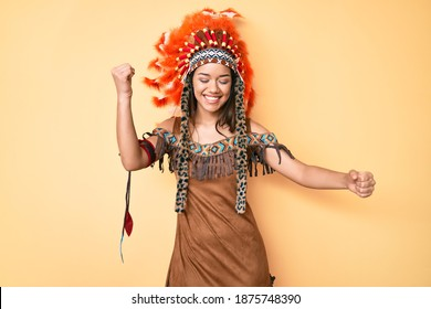 Young beautiful latin girl wearing indian costume dancing happy and cheerful, smiling moving casual and confident listening to music