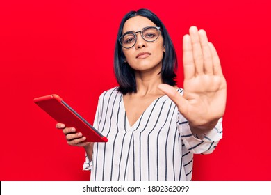 Young beautiful latin woman holding touchpad with open hand doing stop sign with serious and confident expression, defense gesture  - Shutterstock ID 1802362099