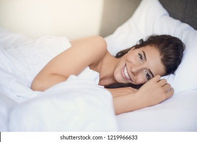 Young beautiful latin woman woman with long brunette hair lying in her bed with white sheets smiling at the camera