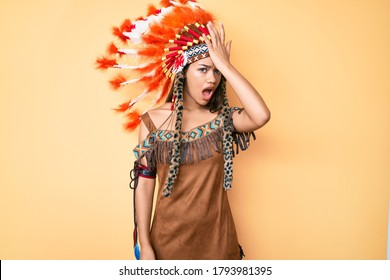 Young beautiful latin woman wearing indian costume surprised with hand on head for mistake, remember error. forgot, bad memory concept.