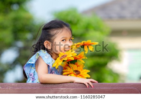 Young beautiful little asian girl holding and smelling sunflower in  playground. Young girl with flower 4b9a5b209