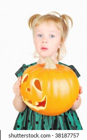 Young beautiful little girl in green dress with a Halloween pumpkin making funny face isolated on the white.