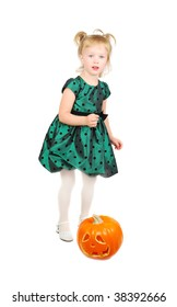 Young beautiful little girl in green dress running for  a Halloween pumpkin isolated on the white.