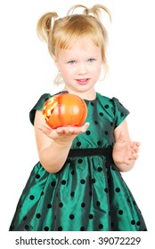 Young beautiful little girl in green dress with a Halloween pumpkin isolated on the white.