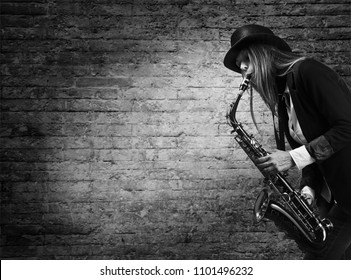 Young beautiful long haired blonde in black hat with saxophone. Woman plays the saxophone against the background of an old brick wall. Black and white , copy space .