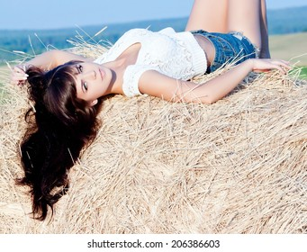 young beautiful long haired girl posing in shorts lying on a haystack.