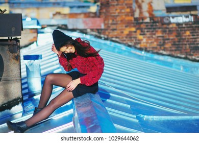 A young beautiful long-haired hipster girl in a short skirt sits on the roof, closing her eyes from the sun, and laughs cheerfully.