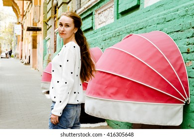 Young beautiful long-haired hipster girl near her home. Lifestyle portrait of a trendy woman entering the door of her house. Concept of freedom and happiness.