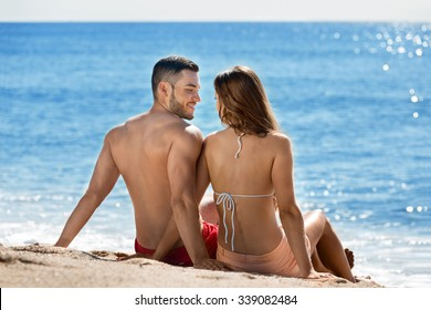 Young  beautiful  lovers sunbathing at sandy beach in vacation