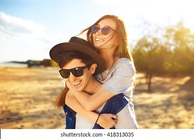 young beautiful loving couple in hipster fashion style posing on a Sunny beach in the shirt t-shirt baseball cap and sunglasses, happily smiling and laughing. outdoor close up portrait