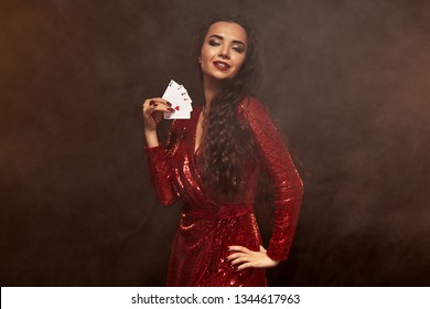 Young beautiful lucky brunette in a red evening dress shows her cards, a four of aces