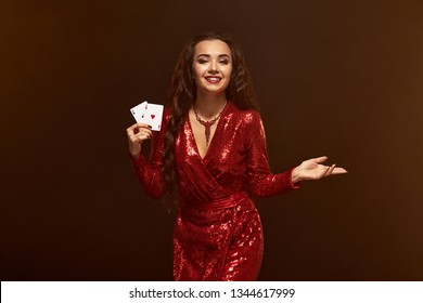 Young beautiful lucky brunette in a red evening dress shows her cards, a pair of aces