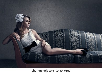 Young beautiful luxurious woman lying on a vintage couch