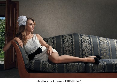 Young beautiful luxurious woman sitting on a vintage couch