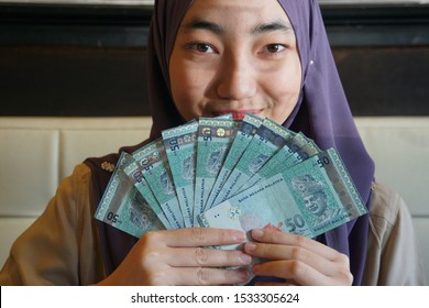 Young Beautiful Malaysian Muslim woman holding Ringgit notes