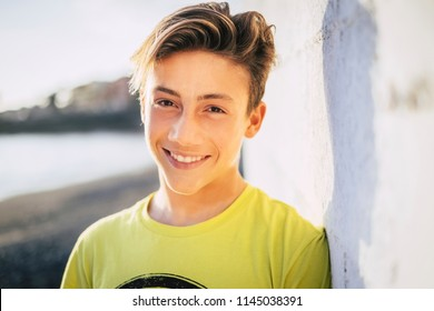 young beautiful male teenager smile outdoor with a blue sky background. summer style concept image