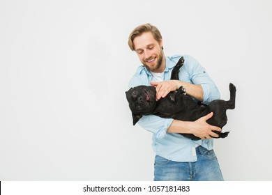 young and beautiful man holding his dog in his arms with love and playing with him, against a white background