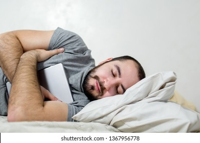 Young and beautiful man sleeps with a tablet in his arms.