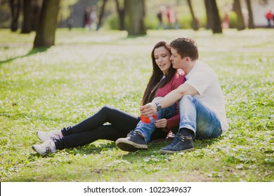 young and beautiful man and woman are sitting together on the grass