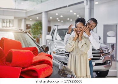 young and beautiful married couple in cars showroom, confident black man buy new car as a present for his wife