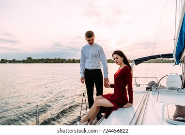 Young beautiful married couple embracing on the yacht on vacation