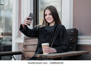 Young beautiful millenial girl in a coat is sitting on an outdor bench with a paper cup of coffee. Autumn or spring day, cool weather. The girl smiles, drinks the drink and takes pictures on the