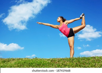 young beautiful mixed race girl doing yoga warrior pose on a beautiful day with clear blue sky. Pretty african american female performing relaxation exercise on a nice spring day. copy space.