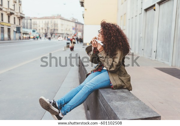 Young beautiful mixed race woman outdoor in the city eating cannolo - sweet, dessert, pastry concept