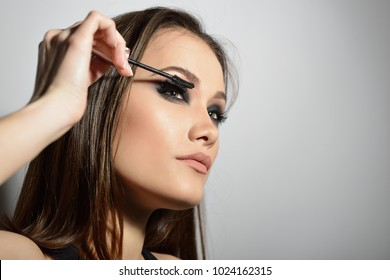 Young beautiful model applying makeup. Fashion girl with mascara. Eyelash makeup.